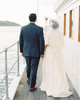 bride and groom walking away next to water