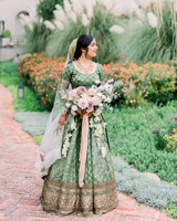 bride wearing green patterned lehenga wedding dress