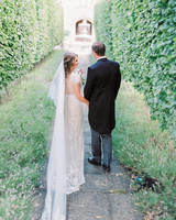 bride and groom standing between shrubs outside