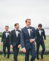 groom and groomsman walking near lake