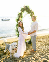 newlyweds with dog on beach