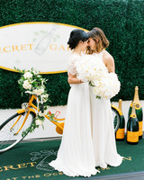 brides standing at orange and white champagne bar