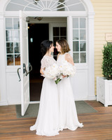 brides face each other outside of wedding venue