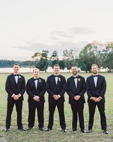 groomsmen posing tuxedos outdoors