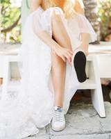 Elizabeth in wedding dress putting on sneakers