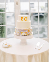 white wedding cake with gold monogram