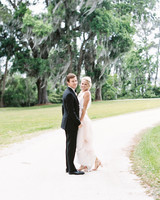 bride and groom poses outdoors on pathway surrounded by trees