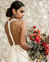 middle part hairstyles bride with sleek updo holding red bouquet
