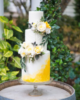 yellow ombre frosted three tiered wedding cake with yellow floral display