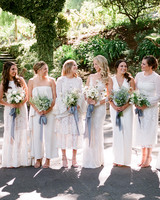 bride with bridesmaids wearing various white dresses