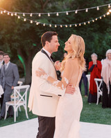 bride and groom first dance outside dance floor string lights