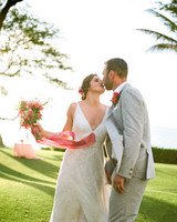 bride and groom kiss on green lawn outside on maui