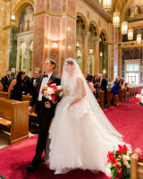 bride and father walk down wedding aisle in church
