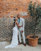 bride and groom posing in front of brick wall