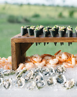 Sushi Rolls on wooden stand above shrimp and oysters