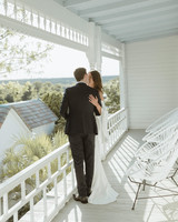 bride and groom kissing on white balcony