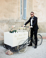 man in tux with white champagne bicycle cart