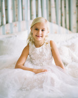flower girl sitting in matching bridal dress