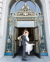 bride and groom celebrate outside city hall after wedding ceremony