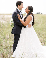 bride and groom smiling at one another in field of tall grass
