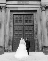 bride and father stand outside church doors before processional