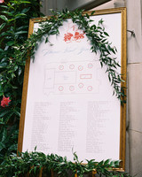 gold framed seating chart accented with greenery
