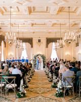 wedding ceremony in ornate gold room decorated with flowers and flower arch