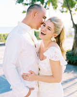 bride wearing white lace dress laughing with groom wearing all white