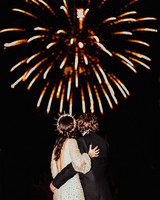 bride and groom stand watching fireworks