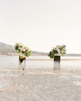 ceremony beach front with mirrored pedestals and white flowers