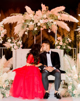 bride and groom kiss while sitting on bench