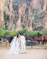 bride and groom kiss near horse ranch by mountains