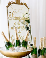 gold Calligraphed Mirror with gold frame on champagne drink table