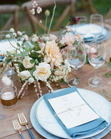 blue tableware and linens on brown wood table with floral centerpieces