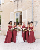 bride surrounded by bridesmaids wearing red floor length gowns