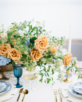 centerpiece with orange garden roses and blue hydrangeas