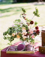 merlot hued yarmulkes in wood tray on table with matching flowers