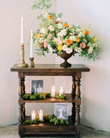 shelving unit with old photos candles and floral arrangement