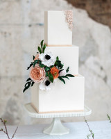 three tiered bas-relief white wedding cake with floral accent