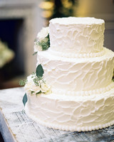 Traditional Three-Tiered White Wedding Cake with White Flowers and Green Leaves