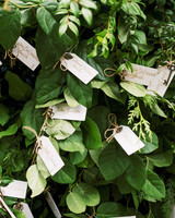 tied escort cards to greenery covered fence