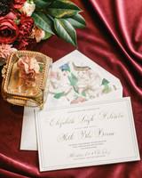 elizabeth seth wedding invitation against red drapery background