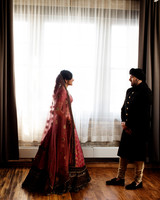 bride and groom share first look in event space before wedding