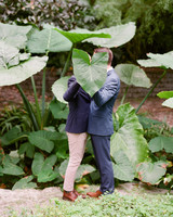 couple grooms kiss behind large leaf outside