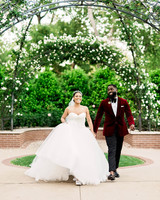 bride and groom walking under garden arch