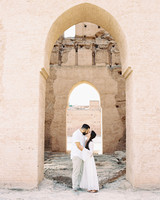 bride and groom kiss under outdoor archway
