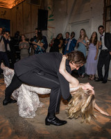 wedding couple first dance dip low as guests watch
