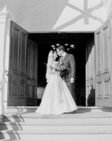 bride and groom stand outside church during wedding recessional