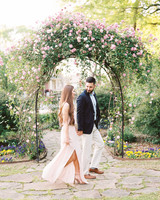 couple walking under floral arch engagement
