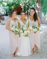 wedding bridesmaids in log v-neck dresses holding flowers